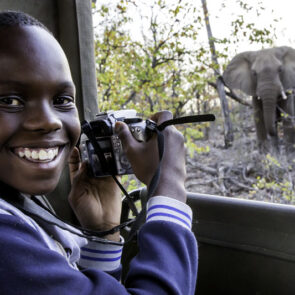 immagine ragazzino che sorride scattando foto ad un elefante del progetto GITZO LÈGENDE di Vitec Imaging Solutions