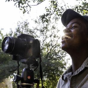 immagine con soggetto che scatta foto e sorride del progetto GITZO LÈGENDE di Vitec Imaging Solutions
