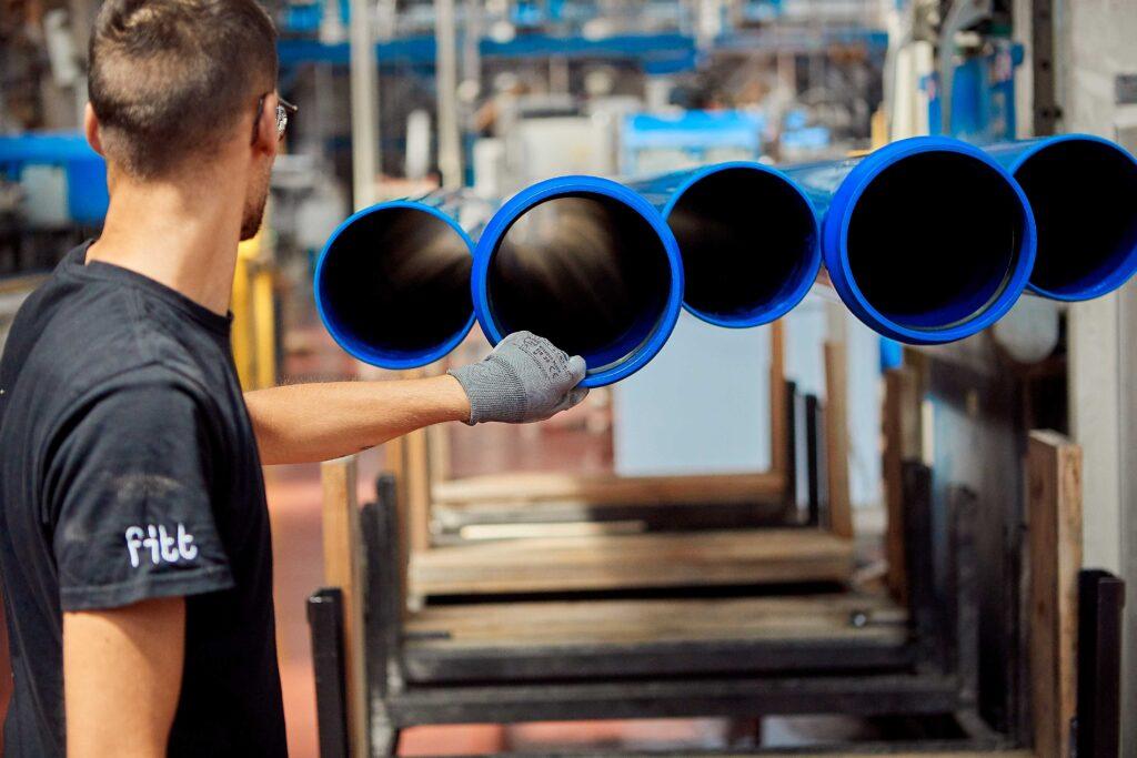 immagine di uomo al lavoro con tubi blu